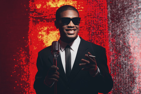 fifties: Smoking retro fifties latin american singer with sunglasses in front of red reflective background.