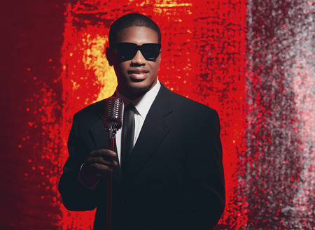Retro 1950s male latin american singer with sunglasses in black suit and tie. Red reflections background. Stock Photo