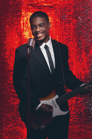 50s: Smiling retro 50s african american singer guitarist in black suit and tie. Red reflective background.