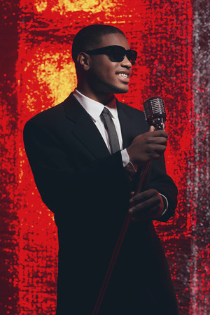 fifties: Retro fifties male african american singer with sunglasses in black suit and tie. Red reflective background.