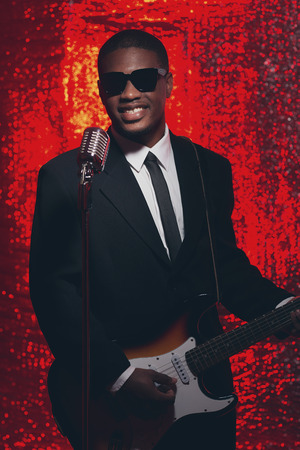 50s: Smiling vintage 50s hispanic singer guitarist in black suit and tie. Red reflective background. Stock Photo
