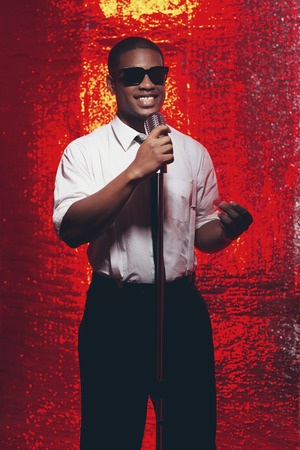 fifties: Smiling vintage fifties hispanic singer with sunglasses in white shirt and tie. Against red reflective background. Stock Photo