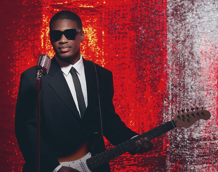 50s: Retro 50s african american singer guitarist in black suit and tie. Red reflective background.