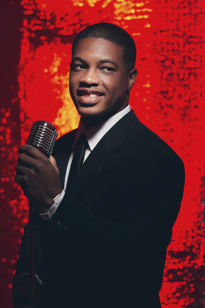 50s: Smiling retro 50s male african american singer in black suit and tie. Red reflective background. Stock Photo