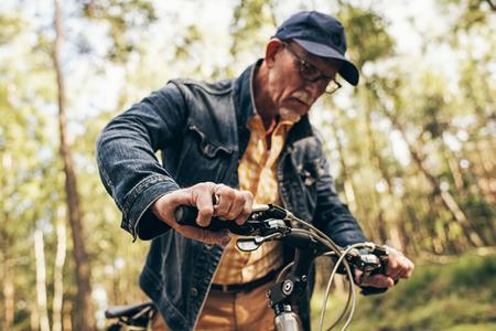 frenos: hombre se retiró en el bosque de revisar los frenos de la bicicleta.