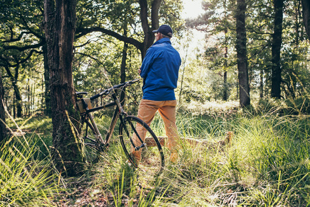 faraway: Man standing in forest looking faraway. Bicycle standing against tree. Rear view. Stock Photo