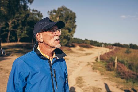 heathland: Active senior man enjoying view of heathland.
