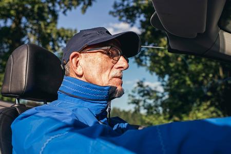 interior shot: Interior shot of retired man driving sports car in summer. Stock Photo