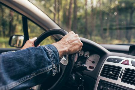 interior shot: Hands of man on steering wheel of car. Interior shot.