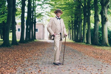 hombre con sombrero: Dandy ricos retro senior en traje de pie con la caña en avenida.