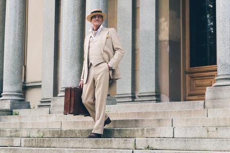 down the stairs: Viajante vintage caminando por las escaleras en la puerta delantera.