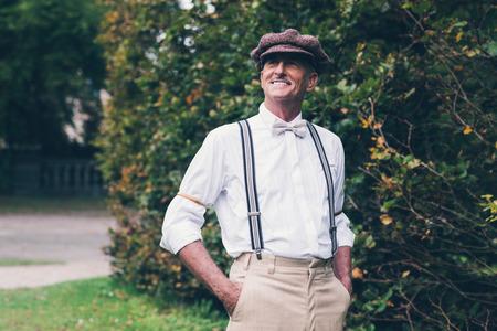 46919966 - Hombre mayor sonriente moda vintage disfrutando de su jardín. 0c0efa133dd