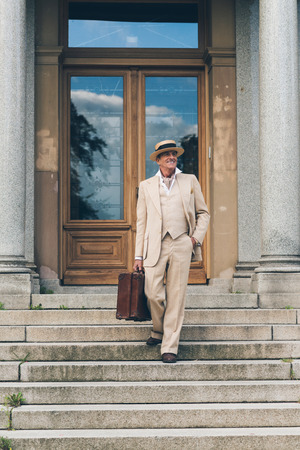 down stairs: Viajante vintage caminando por las escaleras en la puerta delantera.