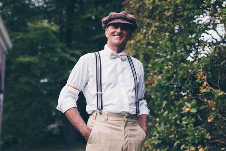 Smiling senior vintage fashion man enjoying his garden.