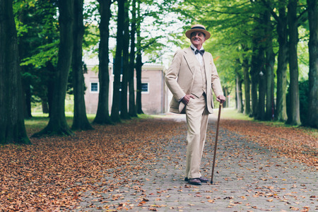 dandy: Smiling wealthy senior retro dandy in suit standing with cane in avenue. Stock Photo