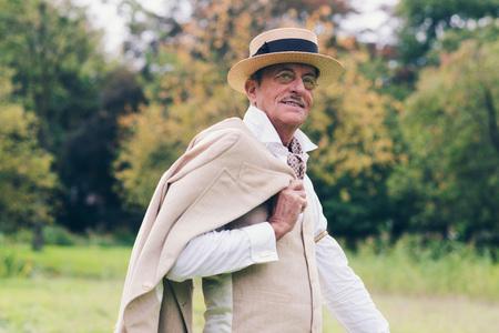 46918040 - Sonriente hombre de negocios de alto nivel época la celebración  de la chaqueta sobre el hombro de pie en el jardín. 1183f126272