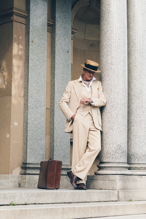 white suit: Retro commercial traveler waiting on stairs leaning against column.