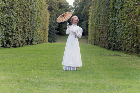 Victorian fashion woman holding parasol standing on lawn with tall hedge.