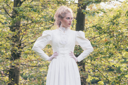 Retro victorian fashion woman in front of trees. Stock Photo