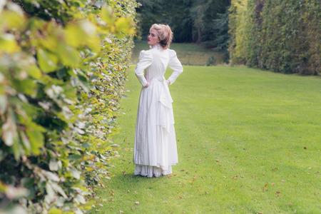 over the shoulder: Vintage victorian woman walking in garden looking over shoulder.