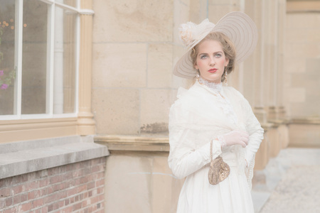 chic woman: Chic victorian woman with hat in front of mansion. Stock Photo