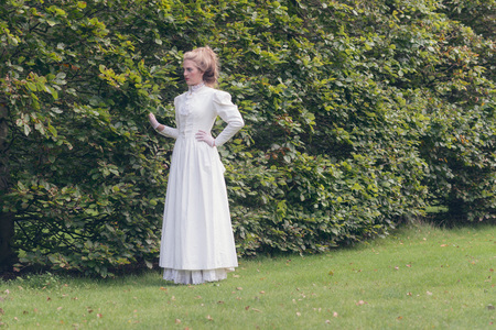 woman dress: Retro victorian woman walking in garden touching tall hedge.