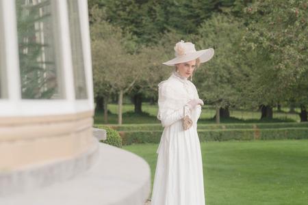looking in corner: Posh victorian woman with hat looking around corner of building.