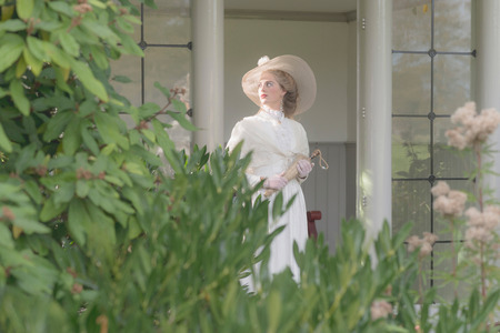 white  hat: Vintage posh victorian woman with hat standing in bower. Stock Photo