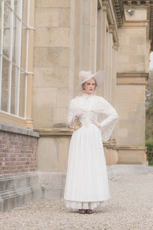 chic woman: Chic victorian woman with hat walking along mansion.