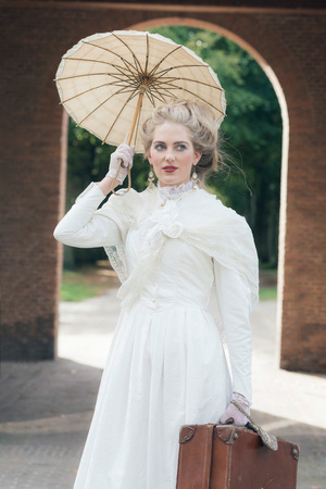 the caucasian beauty: Victorian fashion girl with umbrella standing in front of gate.