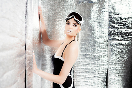 black makeup: Futuristic blonde woman in swimsuit and goggles. Standing in reflective room.