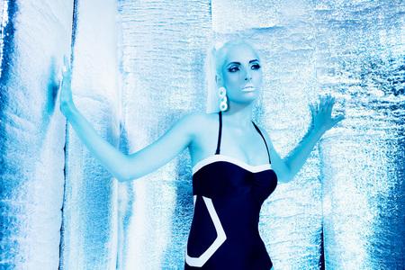 futurism: Futuristic swimwear girl standing in silver reflective room. Stock Photo