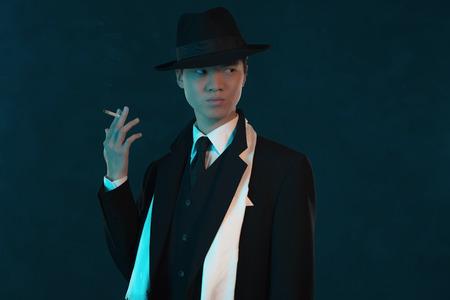hitman: Retro 1940 asian gangster fashion man. Holding cigarette.