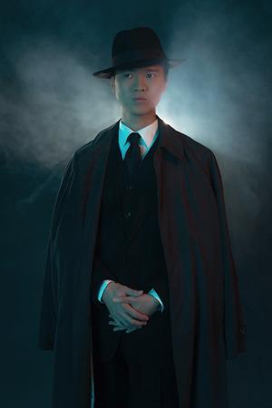 hitman: Scary retro 1940 asian gangster fashion man. Wearing long coat.