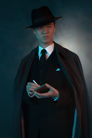 Scary retro 1940 asian gangster fashion man. Holding cigarette box. Wearing long coat. Stock Photo