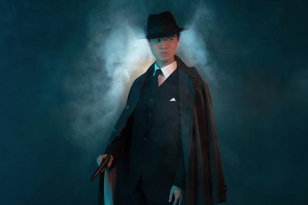 hitman: Dangerous retro 1940 asian gangster fashion man in long coat. Holding gun. Stock Photo