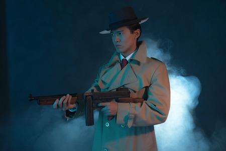 hitman: Vintage 1940 asian gangster fashion man in raincoat. Shooting with gun.