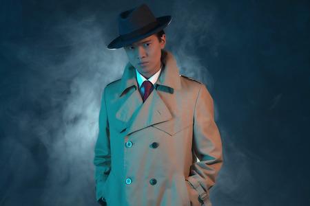 hitman: Mysterious retro 1940 asian gangster fashion man in raincoat. Stock Photo