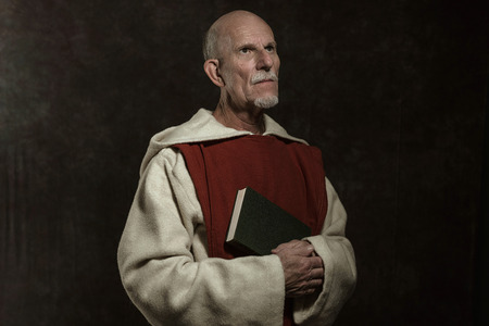 friar: Official portrait of monastic holding book. Studio shot against dark wall.