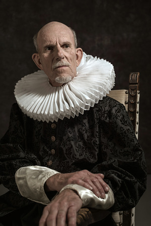 governor: Official portrait of historical governor from the golden age. Sitting in chair. Studio shot against dark wall.