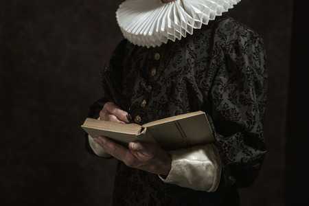 golden age: Hands of historical governor from the golden age. Writing in book. Studio shot against dark wall. Stock Photo
