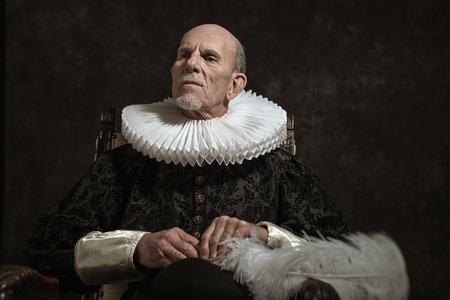 vestidos de epoca: Retrato oficial del gobernador histórica de la época dorada. Sentado en la silla. Estudio de disparo contra la pared oscura.