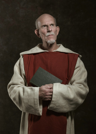 monastic: Official portrait of monastic holding book. Studio shot against dark wall.