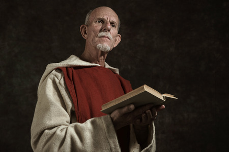friar: Official portrait of monk holding book. Studio shot against dark wall.