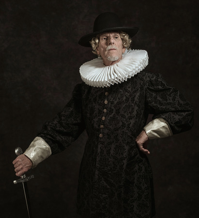 golden age: Official portrait of historical governor from the golden age. Standing with sword. Studio shot against dark wall.
