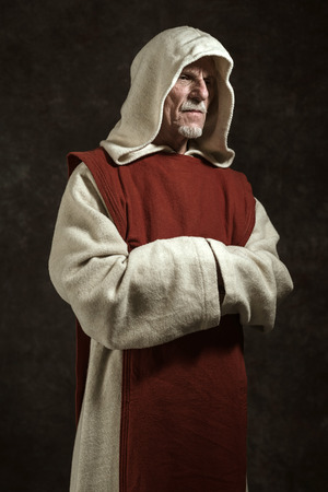 friar: Official portrait of monastic. Studio shot against dark wall.