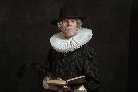 golden age: Official portrait of historical governor from the golden age. Writing in book. Studio shot against dark wall.