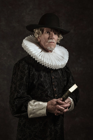 golden age: Official portrait of historical governor from the golden age. Holding a book. Studio shot against dark wall.