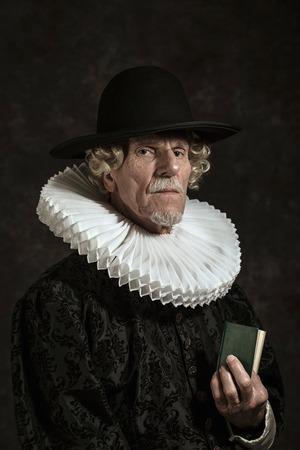 vestidos de epoca: Retrato oficial del gobernador histórica de la época dorada. La celebración de un libro. Estudio de disparo contra la pared oscura.