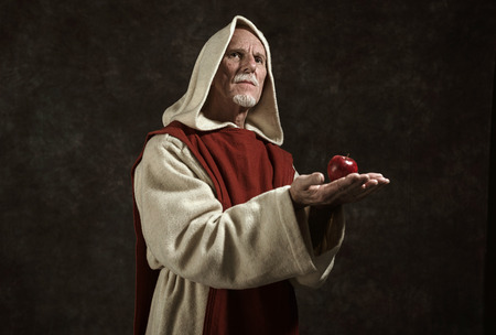 friar: Official portrait of monk holding apple. Studio shot against dark wall. Stock Photo